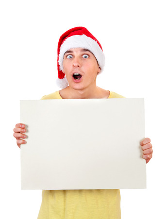 astonish: Surprised Young Man in Santas Hat with Blank Board Isolated On The White Background