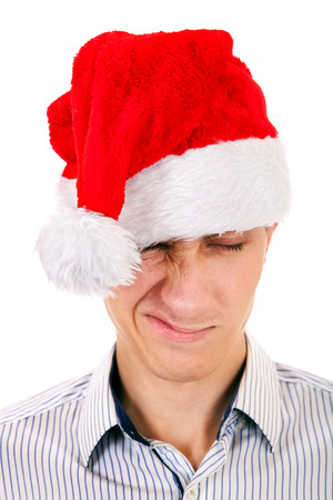vexation: Displeased Young Man in Santa Hat on the White Background Stock Photo