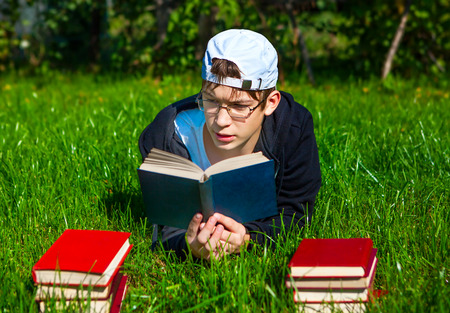 Teenager read a Books on the Grass Stock Photo