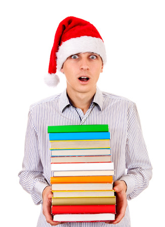 impressed: Surprised Student in Santa Hat with a Books on the White Background