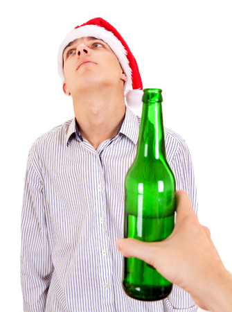 negation: Young Man in Santa Hat refuse a Bottle of the Beer on the White Background Stock Photo