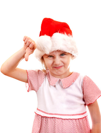 unruly: Annoyed Small Girl in Santa Hat make Thumb Down on the White Background