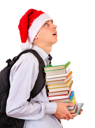 Tired Teenager in Santa Hat with a Books on the White Background