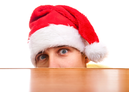 frightful: Frightful Young Man in Santas Hat behind the Table on the White Background