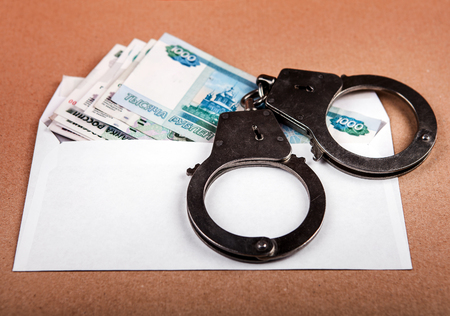 venal: Handcuffs on the Envelope with Russian Rubles on the Table