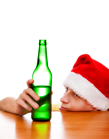 tiredness: Sad Young Man in Santas Hat with the Beer at the Table on the White Background