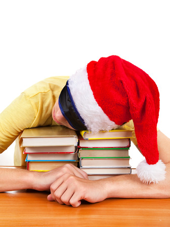 Student in Santa Hat sleep on the Books at the Table Stock Photo