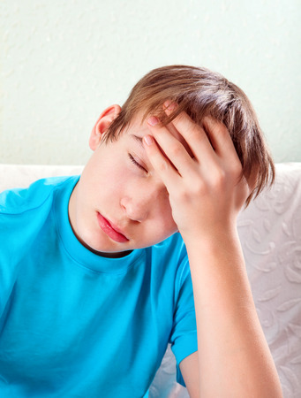 Painful Teenager feel Headache on the Sofa at the Home Stock Photo