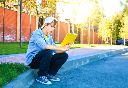 Teenager read a Books on the City Street