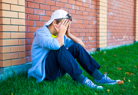 Sad Teenager sit by the Brick Wall outdoor Stock Photo