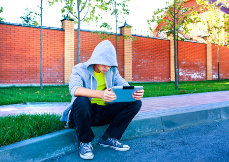 Sad Teenager with Tablet Computer on the Street Stock Photo