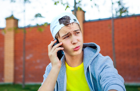 sidewalk talk: Troubled Teenager with Cellphone sit on the City Street Stock Photo