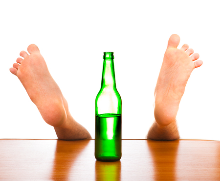Legs and Bottle of a Beer on the Table
