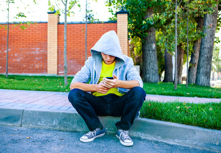 Sad Teenager with Cellphone sit on the City Street
