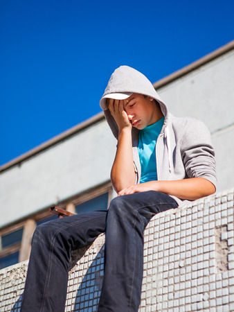 Sad Teenager sit on the Roof Of the Building