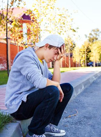 Sad Teenager sit on the City Street Stock Photo