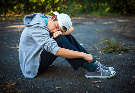 Sad Teenager sit on the Ground outdoor