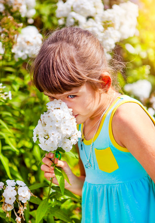 Small Girl with a Flower in the Summer Garden photo