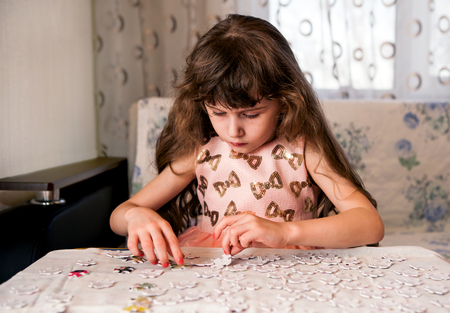 Small Girl solving a Puzzle at the Home photo