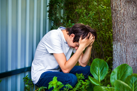 Sorrowful Young Man by the Wall outdoor