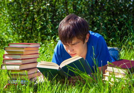 Young Man read a Books on the Grass Stock Photo