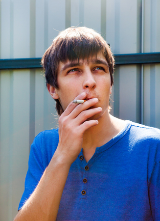 Young Man with Cigarette on the Wall Background outdoor
