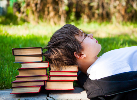 Tired Teenager lying on the Books in the Park
