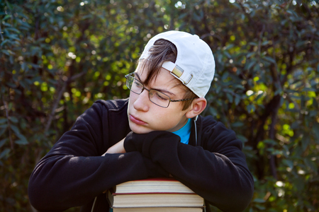apathy: Sad Teenager with a Books on the Nature Background