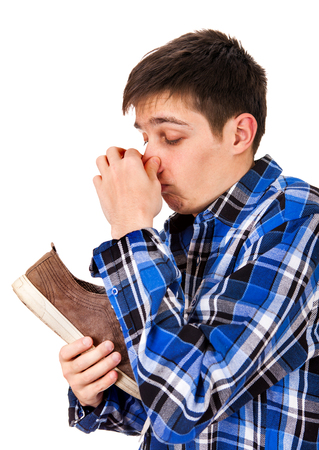 Young Man feel a stinking smell from a Sneaker on the White Background