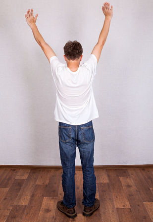 Rear View of the Young Man with Hands Up in the Room