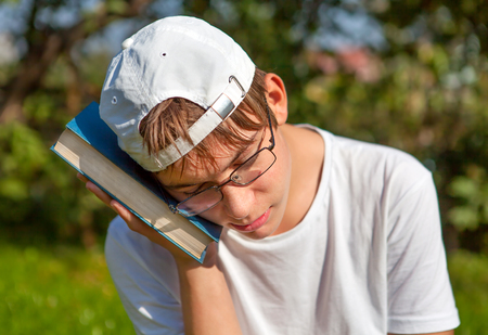 Sad Teenager with the Book in the Summer Park Stock Photo