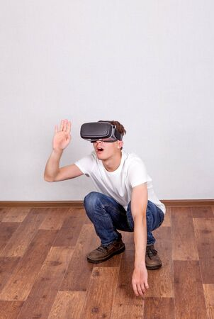 impressed: Surprised Young Man in Virtual Reality Headset on the Floor in the Room Stock Photo