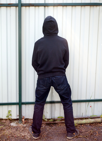 Rear View of Person Pee on the Wall Stock Photo