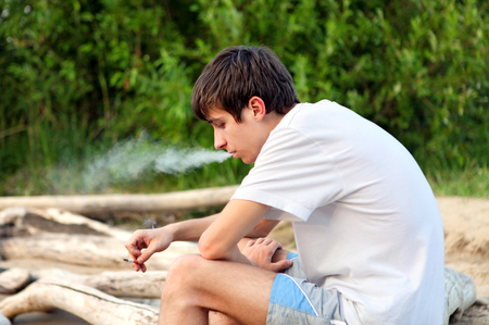 Sad Young Man with Cigarette on the Nature Background