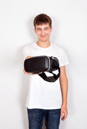 Young Man give a Virtual Reality Headset by the Wall photo