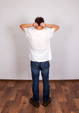 Rear View of Young Man Covering his Ears in the Room photo