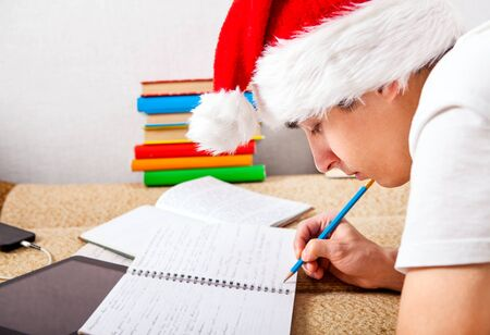 Student in Santas Hat doing Homework on the Couch