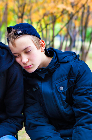 Tired Teenager sleeping on the Friend Shoulder outdoor