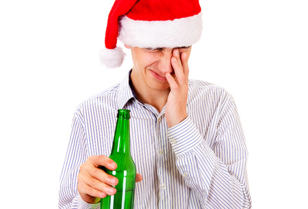 Tired Young Man in Santa Hat with a Bottle of the Beer Isolated on the White Background Stock Photo