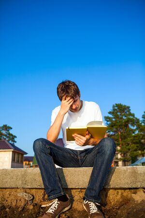 Troubled Young Man read a Book outdoor