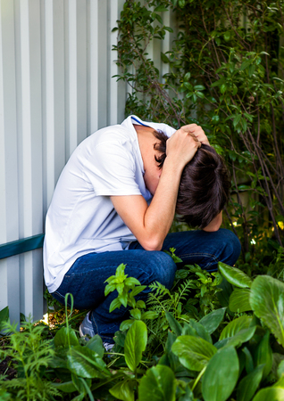 Sad Young Man sit by the Wall outdoor Stock Photo