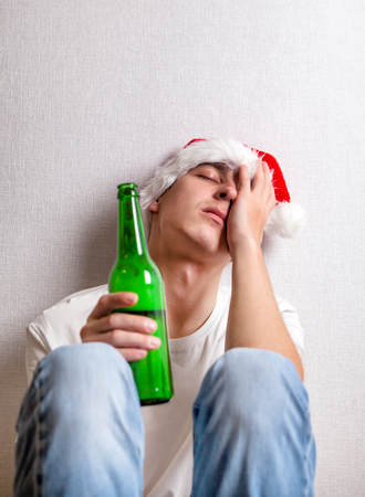 Sad Young Man in Santas Hat with a Beer by the Wall Stock Photo