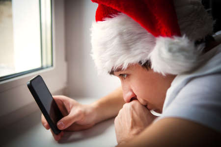 caller: Young Man in Santa Hat with a Phone by the Window