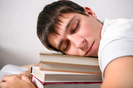 Tired Young Man sleep on the Books in the Room