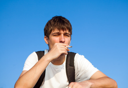 Sad Young Man smoking Cigarette on the Sky Background Stock Photo