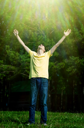 Toned Photo of Happy Young Man with Hands Up on the Nature Background Stock Photo