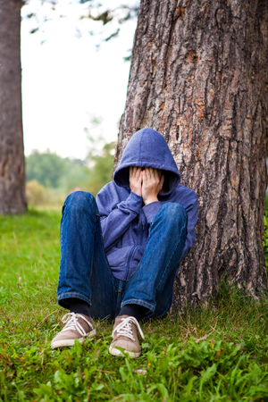 Sad Young Man sit under the Tree in the Park