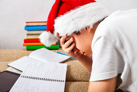 Tired Student in Santas Hat doing Homework on the Couch