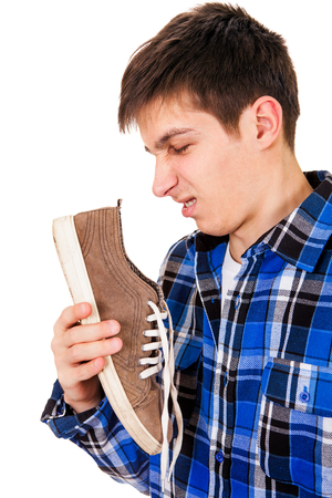 Young Man feel a stinking smell from a Sneaker Isolated on the White Background