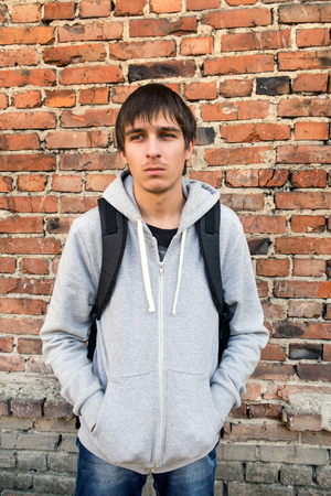 Sad Young Man on the Brick Wall Background Stock Photo